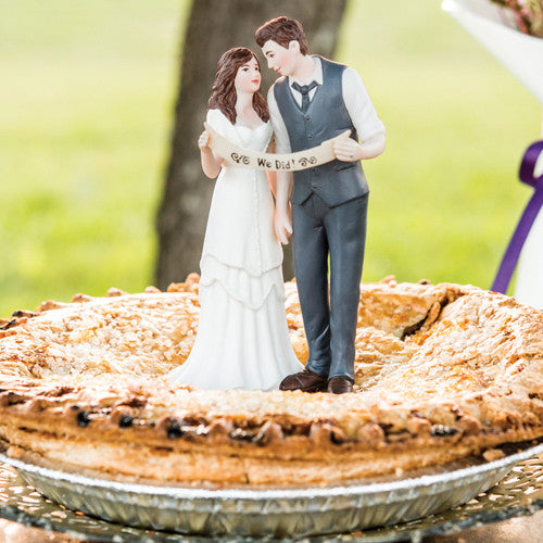 A cute Indie Wedding Couple Porcelain Cake Top on top of a blueberry pie.