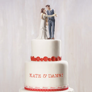 An Indie Wedding Couple Porcelain Cake Top on top of a red and white wedding cake.