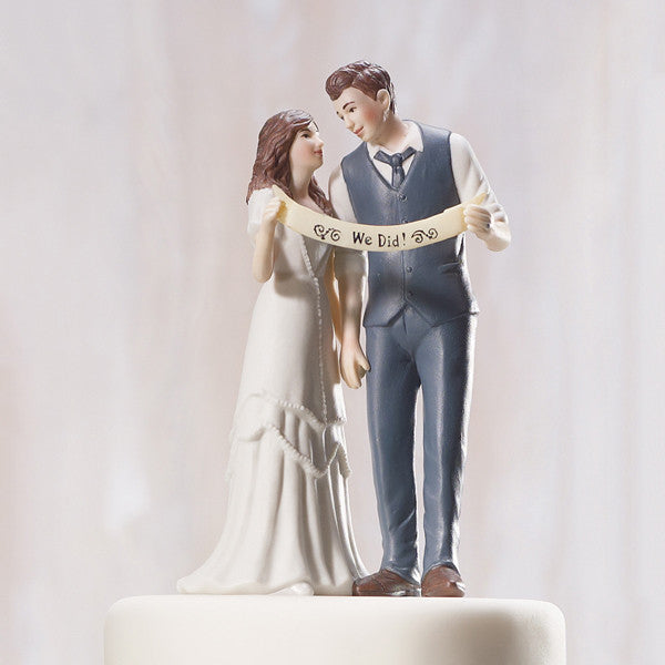 An Indie Wedding Couple Porcelain Cake Top sitting atop an off white wedding cake.