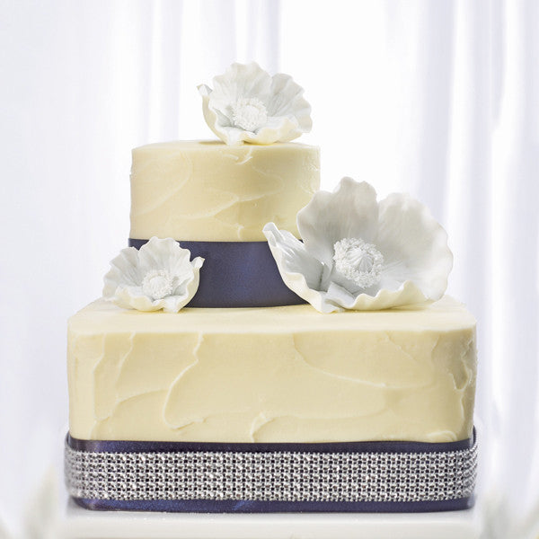 White Poppy Blooms for Wedding Cake atop of a yellow and purple wedding cake with diamond wrap.