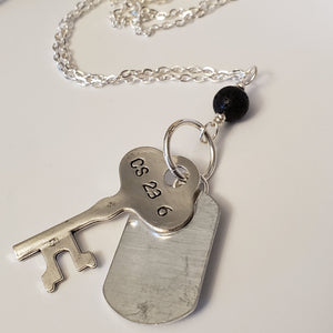 Long chain necklace with key-shaped charm, dog tag and black lava bead