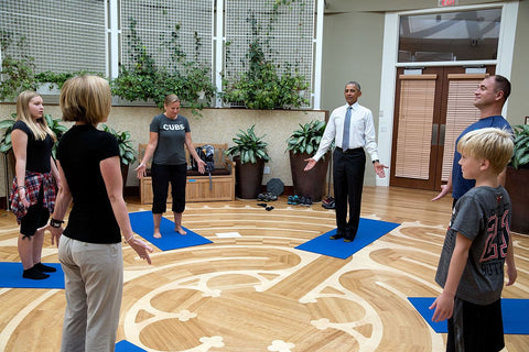 President Obama and military family doing yoga on the NICOE labyrinth