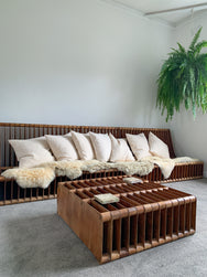 Vintage Mid-Century Timber Sofa with pillows and sheepskins