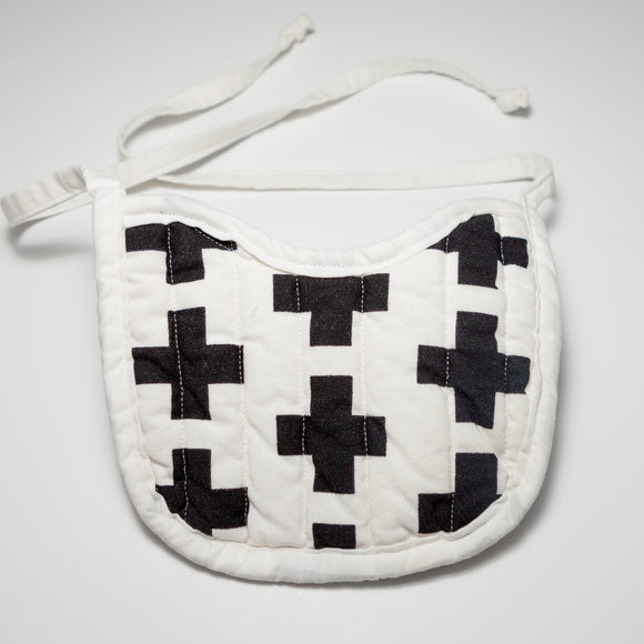 Bespoke Baobei's Matthew quilted bib with black crosses and plaid print and white trim, front.