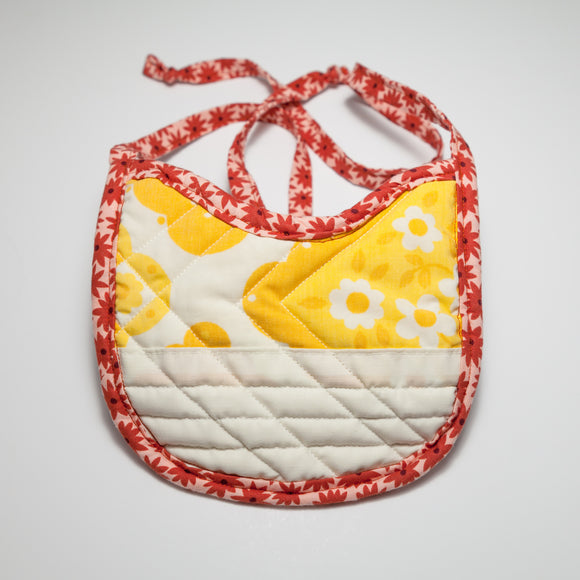 Bespoke Baobei's Jean quilted bib with yellow floral pattern on front with a mock white pocket , paired with a solid denim back. The trim is a red floral pattern. Front.