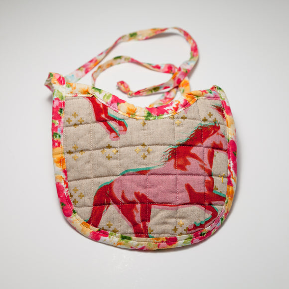 Bespoke Baobei's Nelly quilted bib with pink horses on the front , paired with a pink plaid back. The trim is a red and yellow floral pattern. Front.