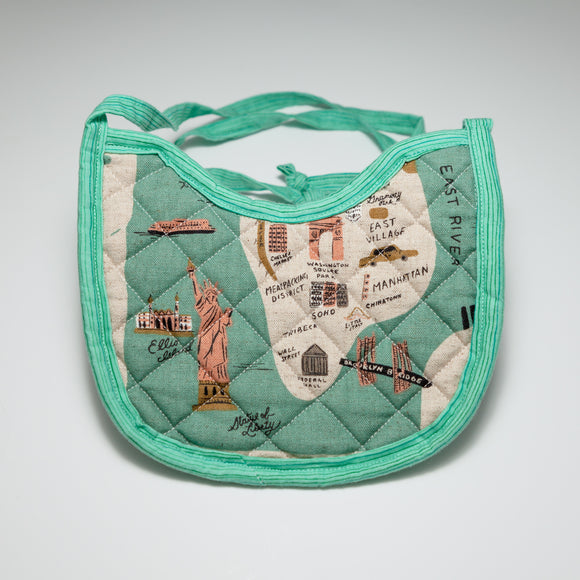 Bespoke Baobei's New York quilted bib with an artist rendition of New York, and a green back. The trim is an aqua green stripe pattern. Front.