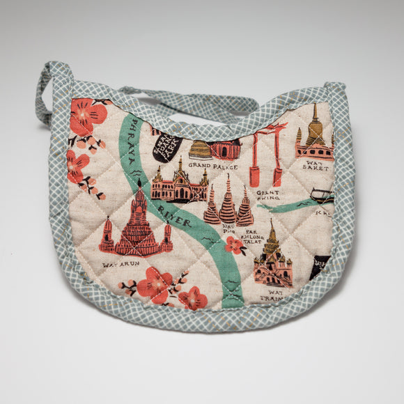 Bespoke Baobei's Bangkok quilted bib with an artist rendition of Bangkok, and a tan back. The trim is a gray crosshatch pattern. Front.