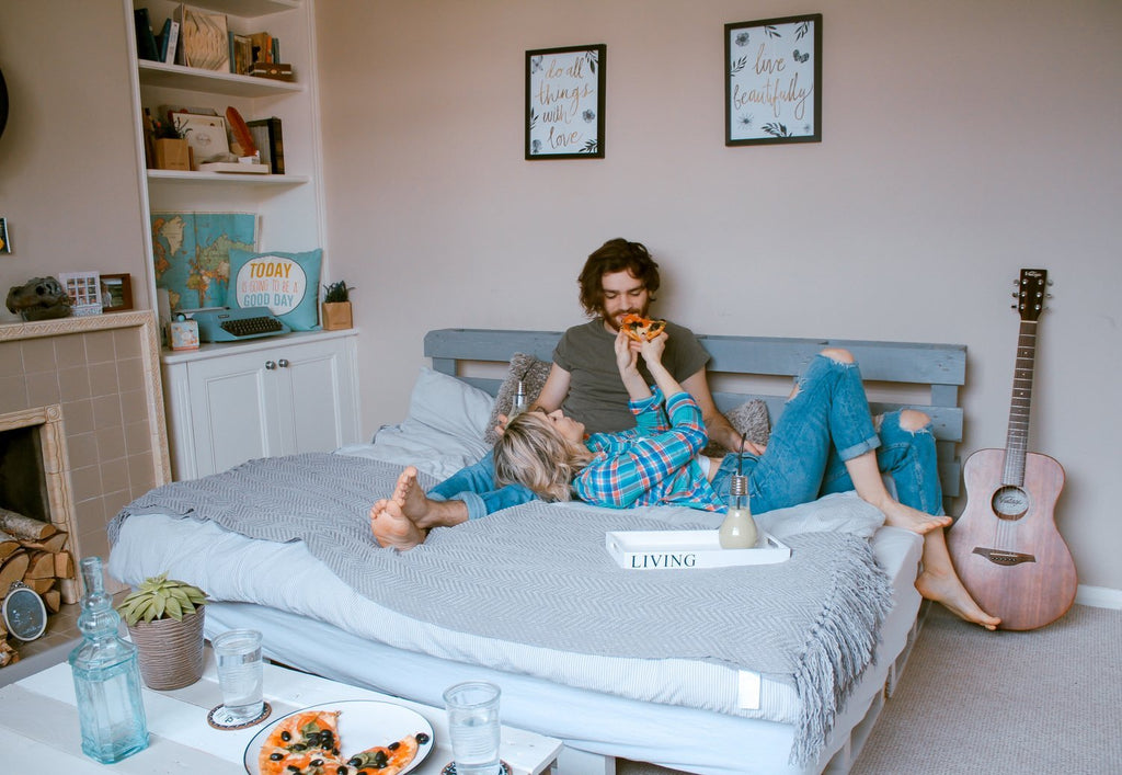Couple relaxing on a bed sharing a pizza