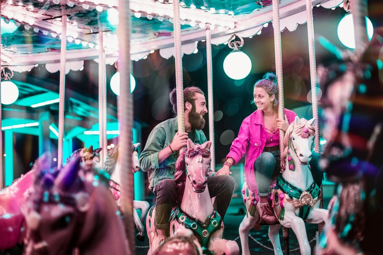 A couple holding hands and smiling at each other on a merry-go round