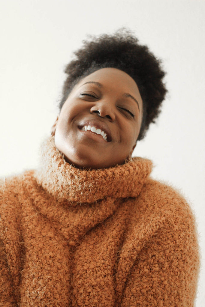 Pleasure is a human right. Picture of a woman wearing a soft warm turtle neck jumper, smiling with her eyes closed.