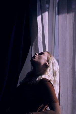 Blonde woman leaning against the window with sun coming through the curtains