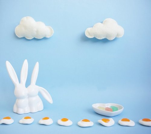 Rabbit figurine in front of a blue background with lollies and clouds for detail