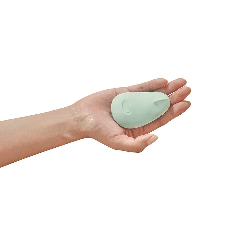 Pom Massager by Dame Products sitting the palm of someones hand, pictured in Jade