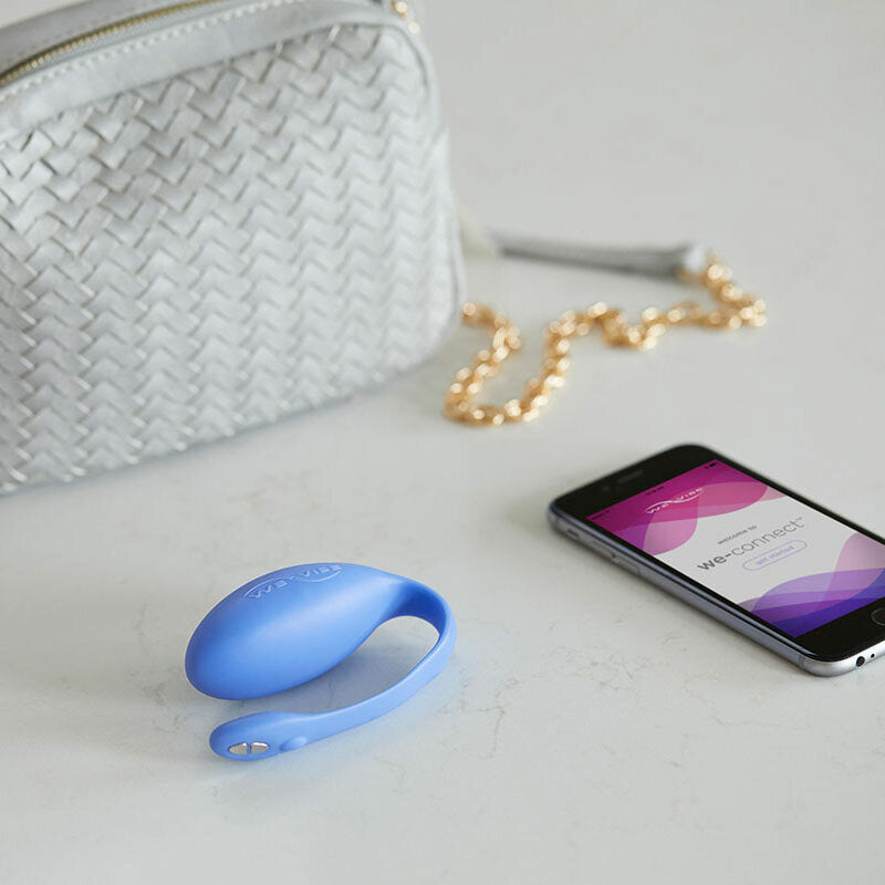 Jive by We-Vibe is a wearable hands-free G-Spot vibrator, pictured next to a  phone with the We-Vibe app on the screen and a white handbag