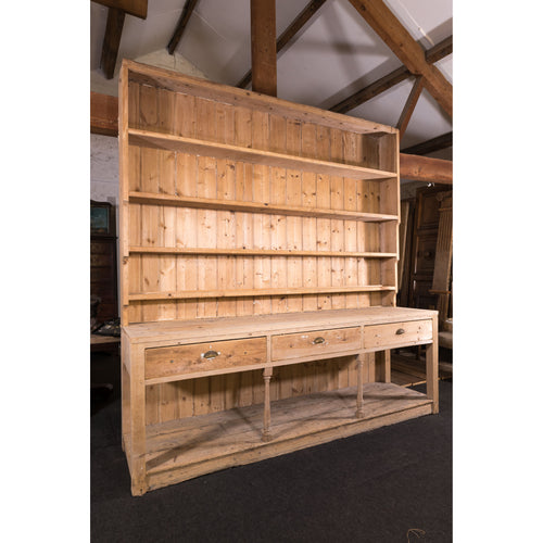 A very large scale antique stripped pine kitchen dresser.