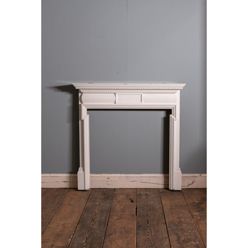 A simple late 19thC painted pine fire surround, with a dentil moulding and central tablet.