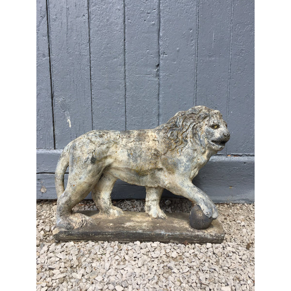 Garden statuary // Weathered composition stone lion with raised paw on ball