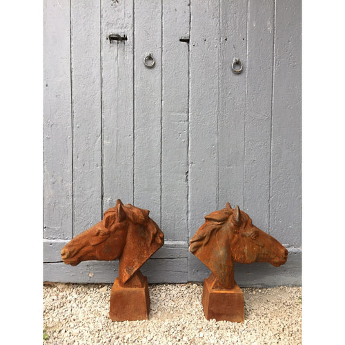 rusty cast iron sculptures of horses heads