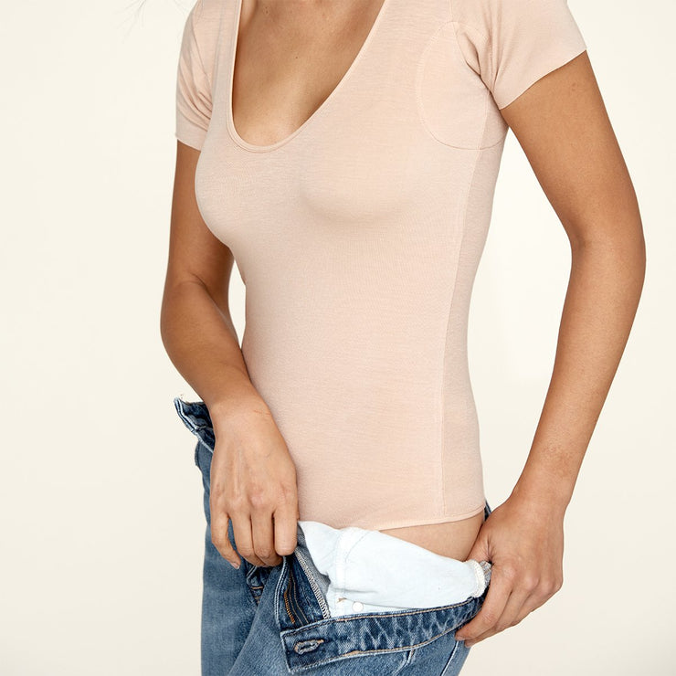 Woman putting on jeans, wearing The Bodysuit, a sweatproof undershirt from Numi in light beige