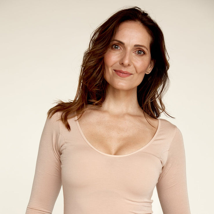 Woman smiling while wearing The Three Quarter undershirt from Numi in light beige