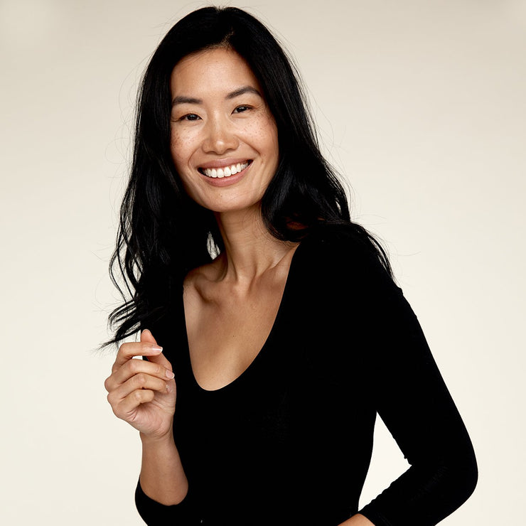 Woman smiling while wearing The Three Quarter undershirt from Numi in black