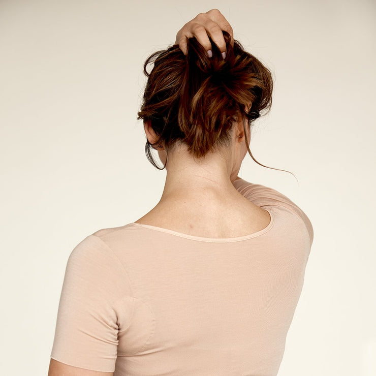 Woman holding her hair up, wearing The Crop undershirt from Numi in light beige