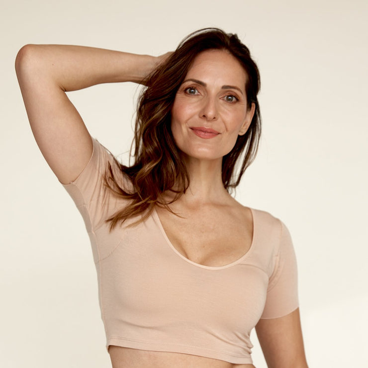Woman with arm up wearing The Crop undershirt from Numi in light beige