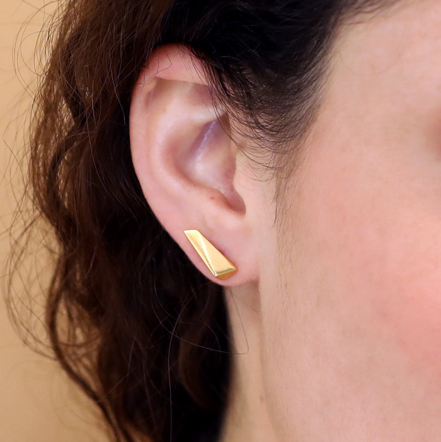Girl wearing elegant small stud gold plated earrings