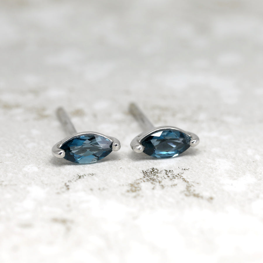 Front view of topaz london blue small earrings studs handmade in montreal fine jewelry designer marquise blue gemstone custom earrings gemstone specialist
