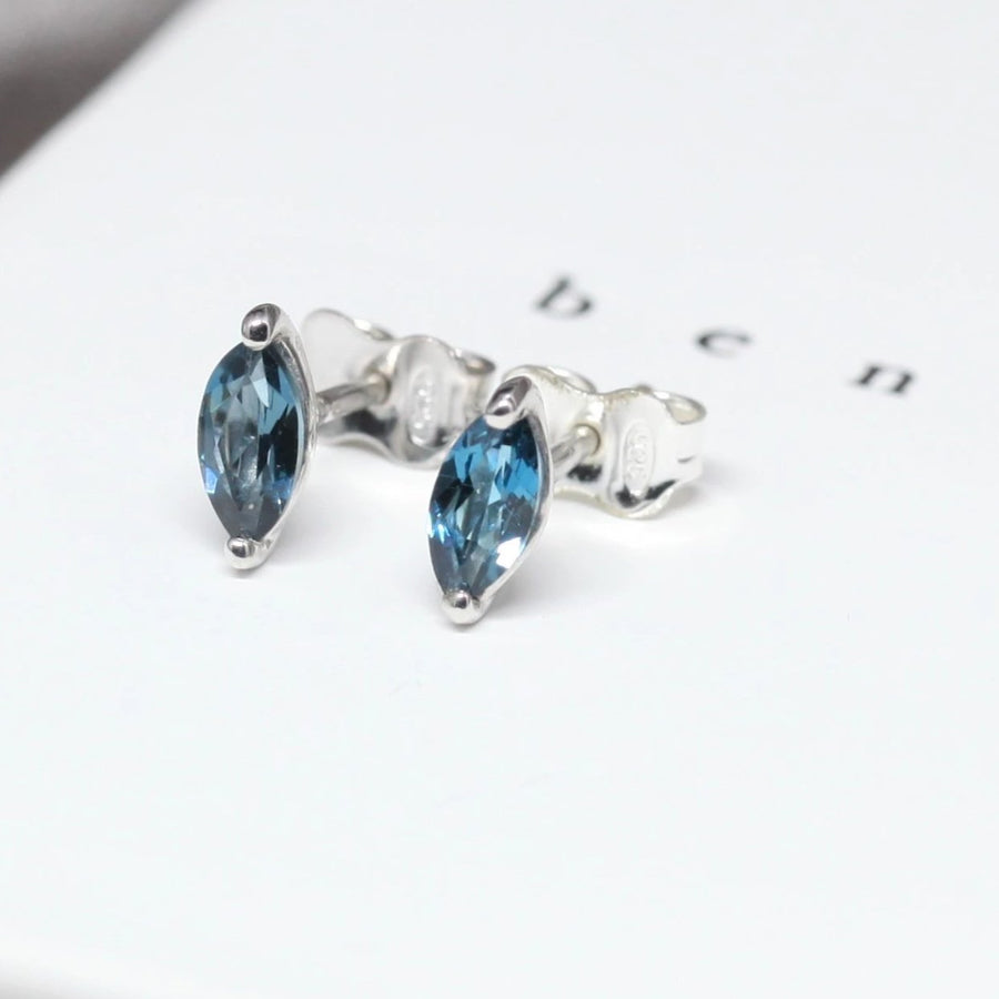Side view of bena jewelry london blue topaz marquise shape small earrings custom color gemstone stud specialist silver earrings bena jewelry montreal fine jewelry designer