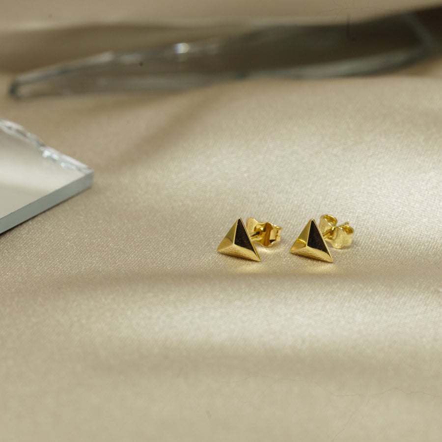 Small vermeil gold stud earrings montreal made on brown slick background bena jewelry montreal custom designer fine jewelry fashion pyramidal small triangle bold volum jewelry design