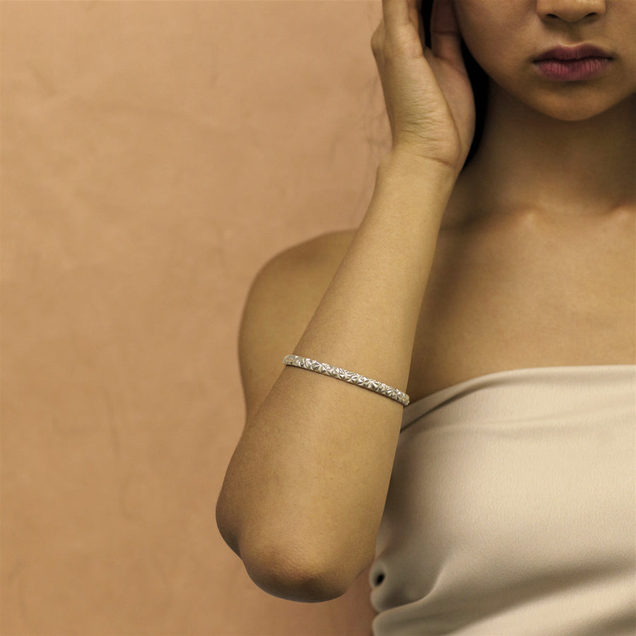 Girl wearing bangle bracelet. Silver jewelry