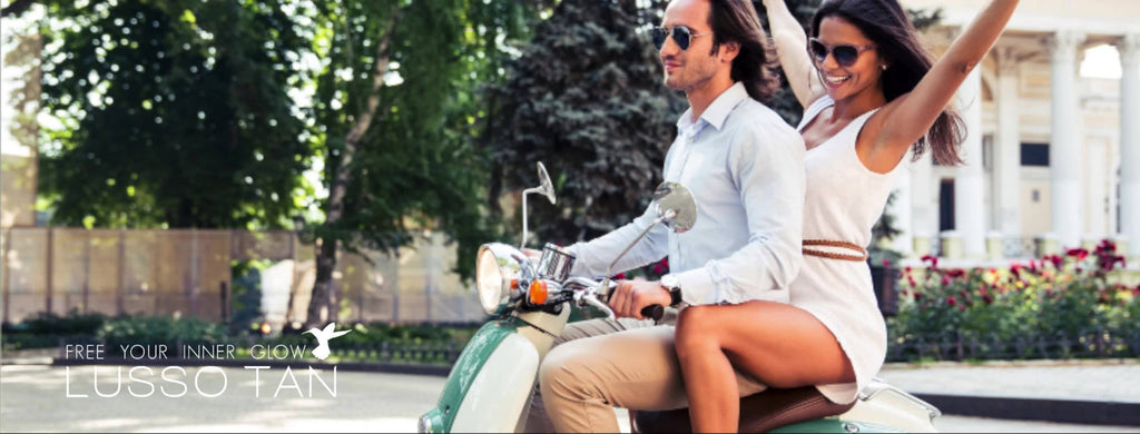 A perfectly tanned woman sitting behind a man on the back of a moped in the mediterranean.