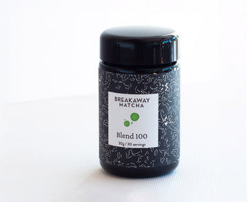 Blend 100, from Nishio, our extremely high-grade matcha,  in a black-violet German glass jar with new kimono-stencil label, 30 grams, sitting on simple paper background.