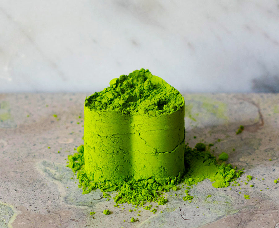 Heart-shaped pile of beautiful matcha, Blend Daphne, sitting on granite.