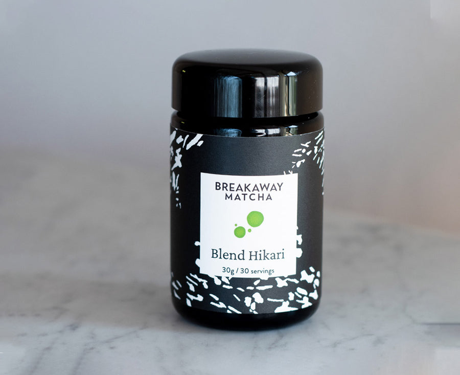 Blend Hikari, our extremely high-grade matcha,  in a black-violet German glass jar with new kimono-stencil label, 30 grams, sitting on granite.