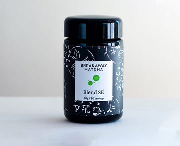 Blend SE, our extremely high-grade matcha,  in a black-violet German glass jar with new kimono-stencil label, 30 grams, sitting on two-tone background.