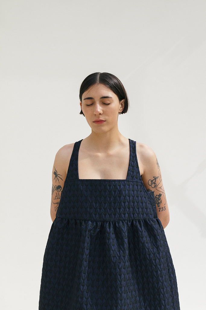 navy and black brocade oversized voluminous strappy dress with shirred empire waist on a white shadow background, model had tattoos eyes closed pale lipstick