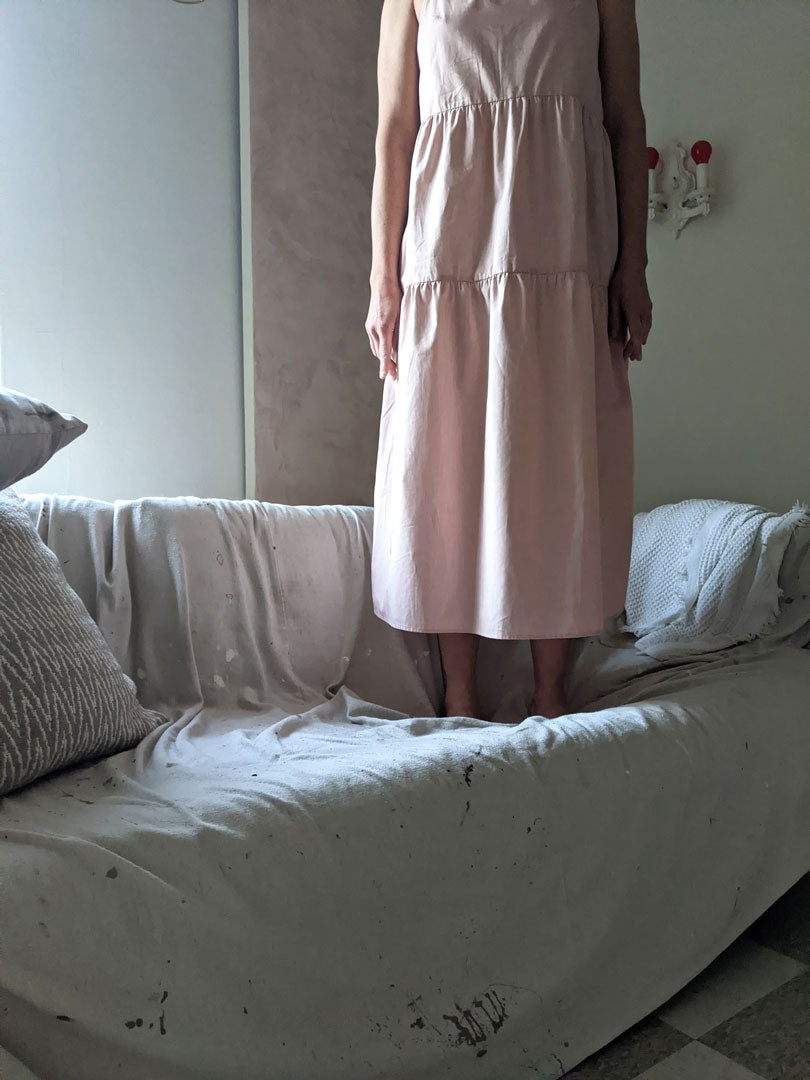 pale pink tiered dress woman standing on sofa in studio with light coming in from behind monotone palette