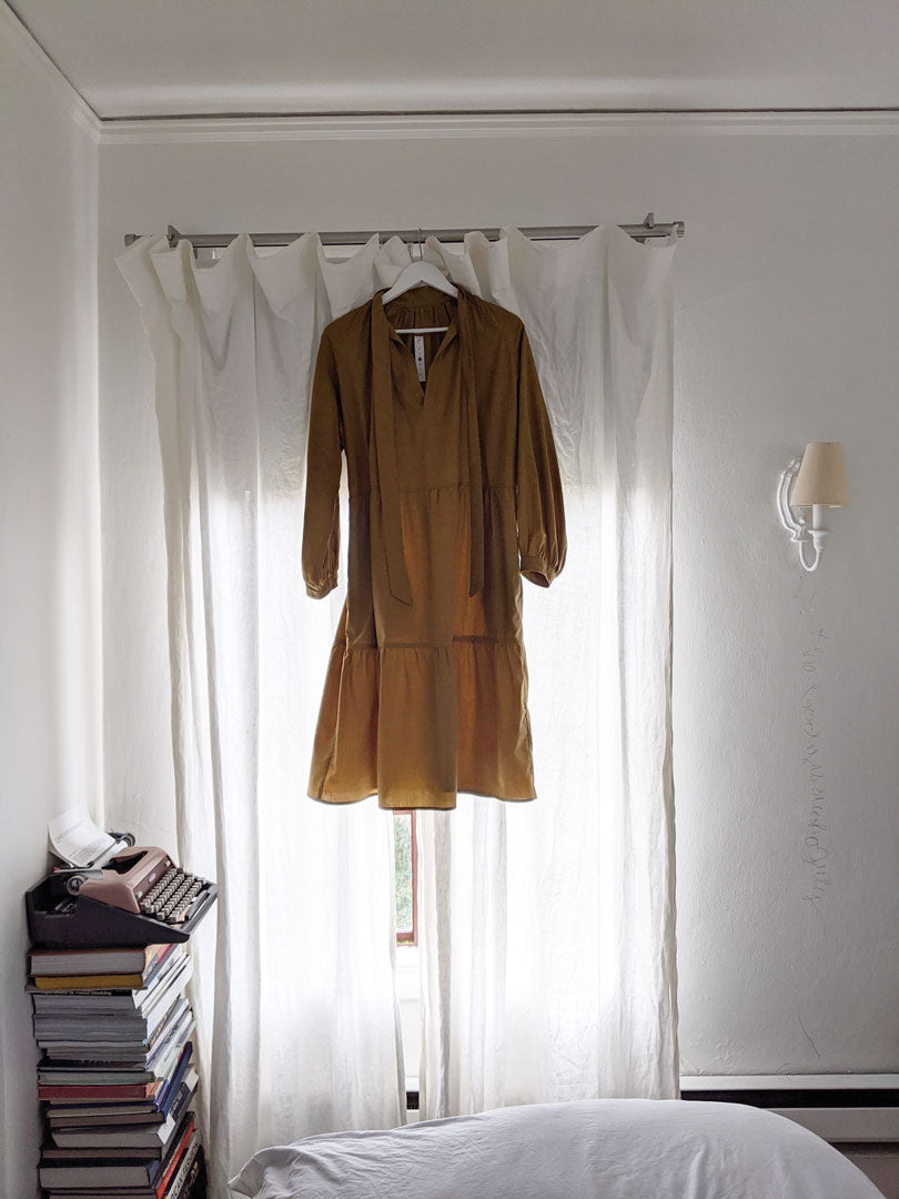 tiered wheat yellow dress with long puffy sleeves and neck ties hanging on curtain rod in front of white curtains with light shining through artists bedroom white bed with old typewriter and stack of books