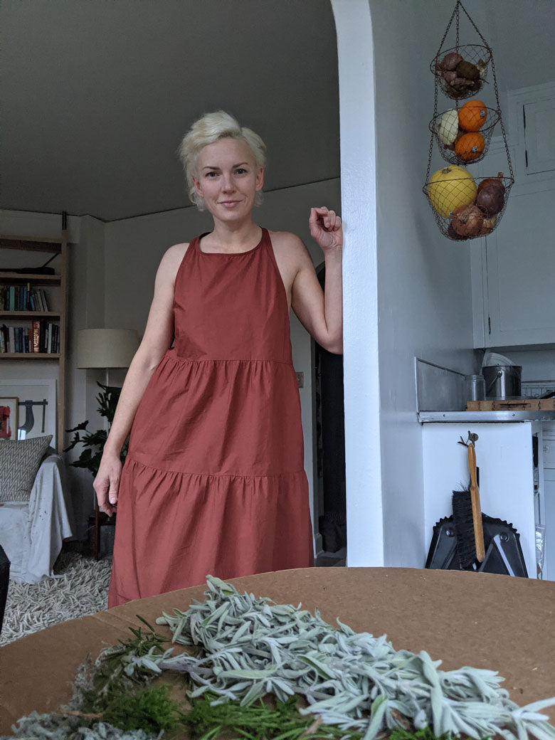 woman smiling with dyed white hair in a rust tiered sleeveless dress in her kitchen with studio in background