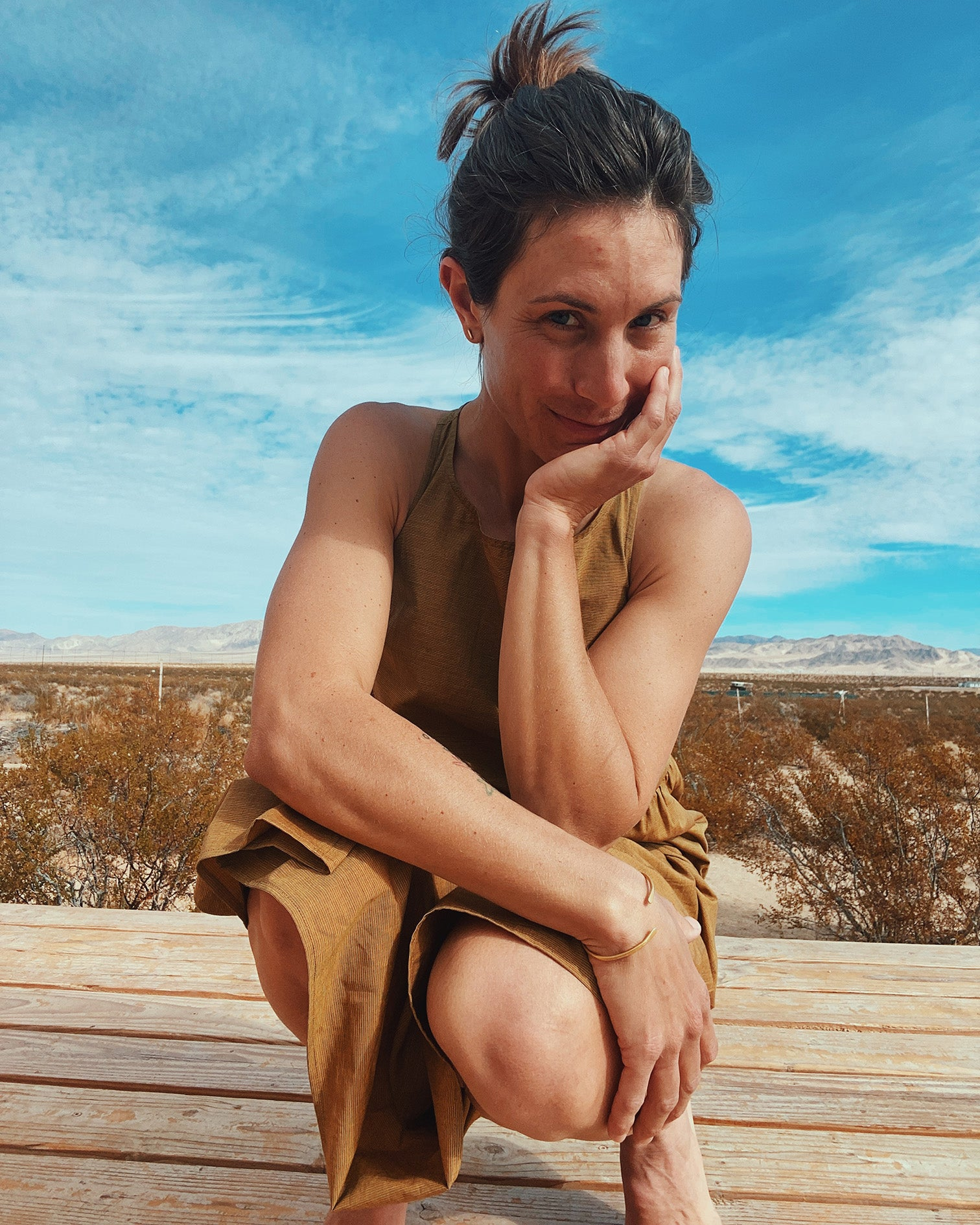 woman in mustard yellow long tiered dress crouching on wood deck looking you straight in the eyes in Joshua Tree with mountains and desert landscape in the background