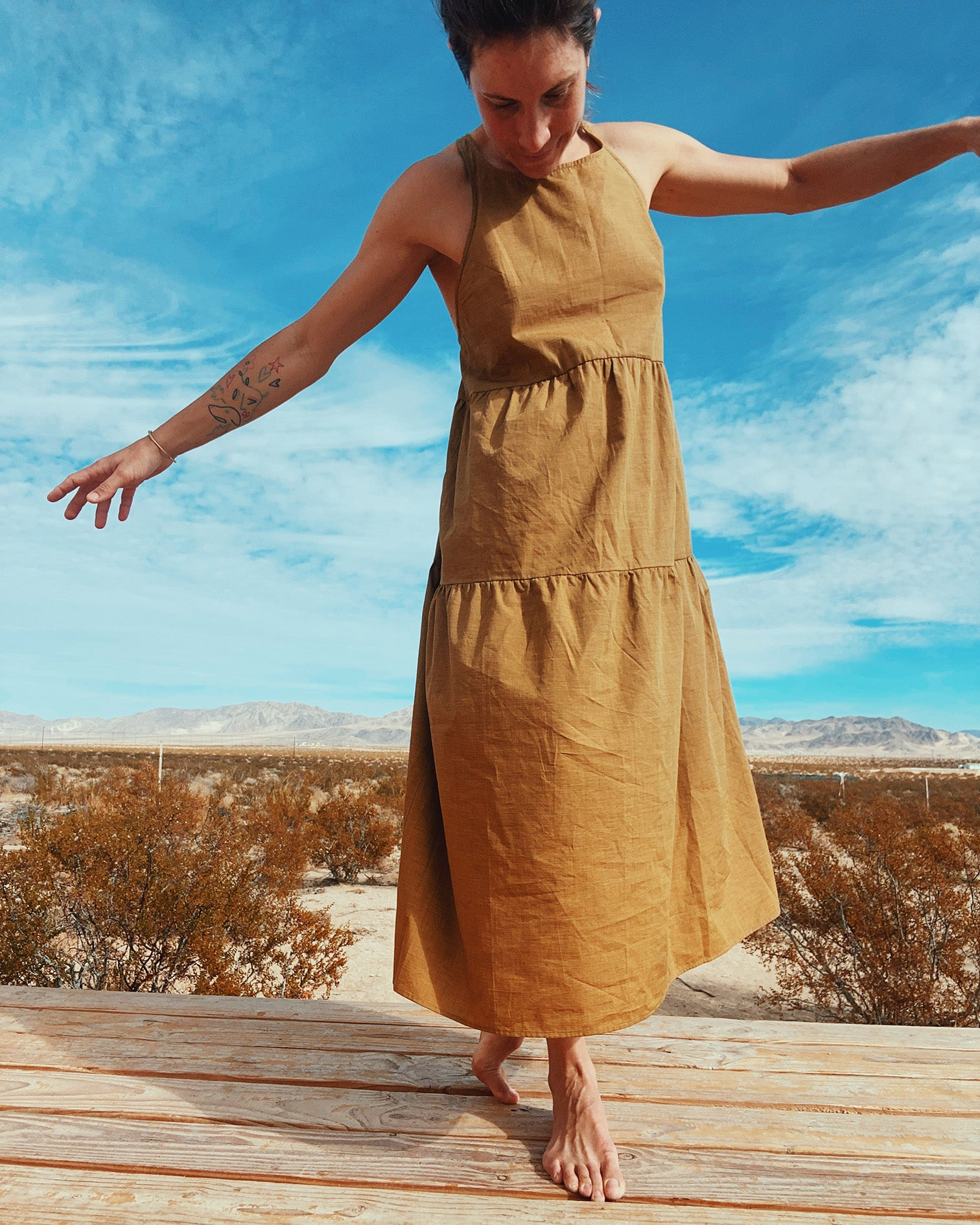 woman in mustard yellow long tiered dress dancing on wood deck in Joshua Tree with mountains and desert landscape in the background
