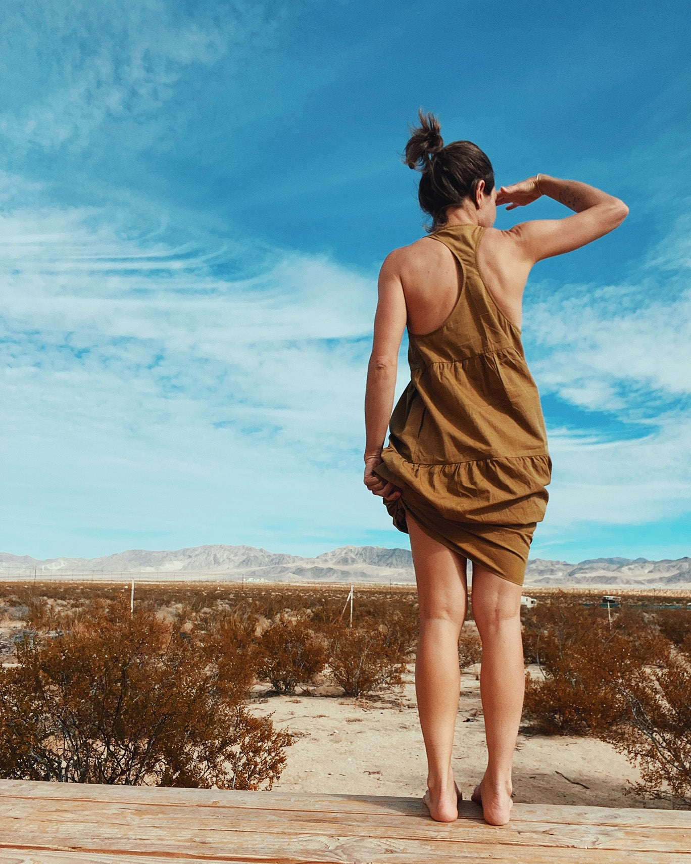 woman in mustard yellow long tiered dress ruched at the hip on wood deck in Joshua Tree with mountains and desert landscape in the background