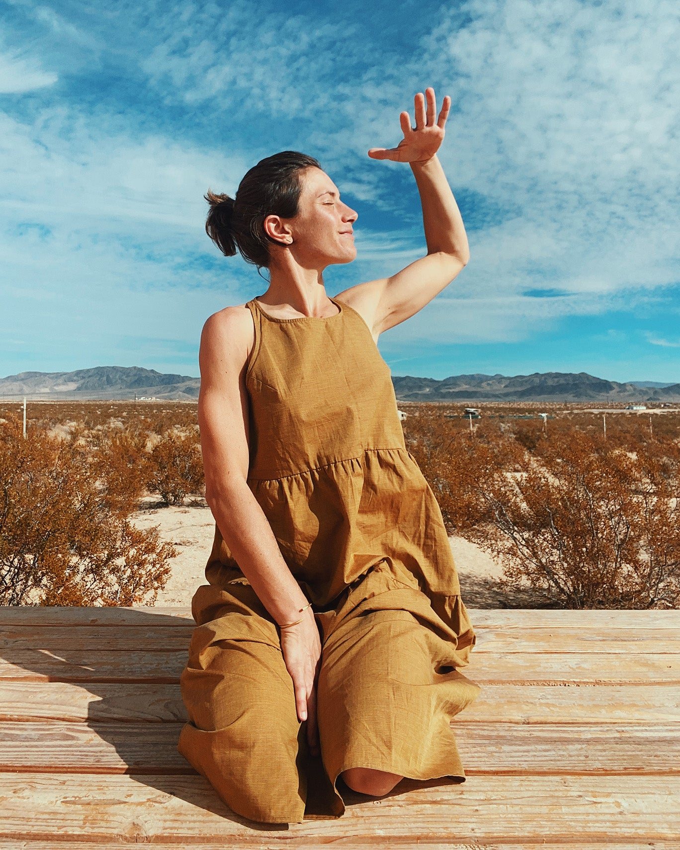 woman in mustard yellow long tiered dress sitting on wood deck in Joshua Tree with mountains and desert landscape in the background