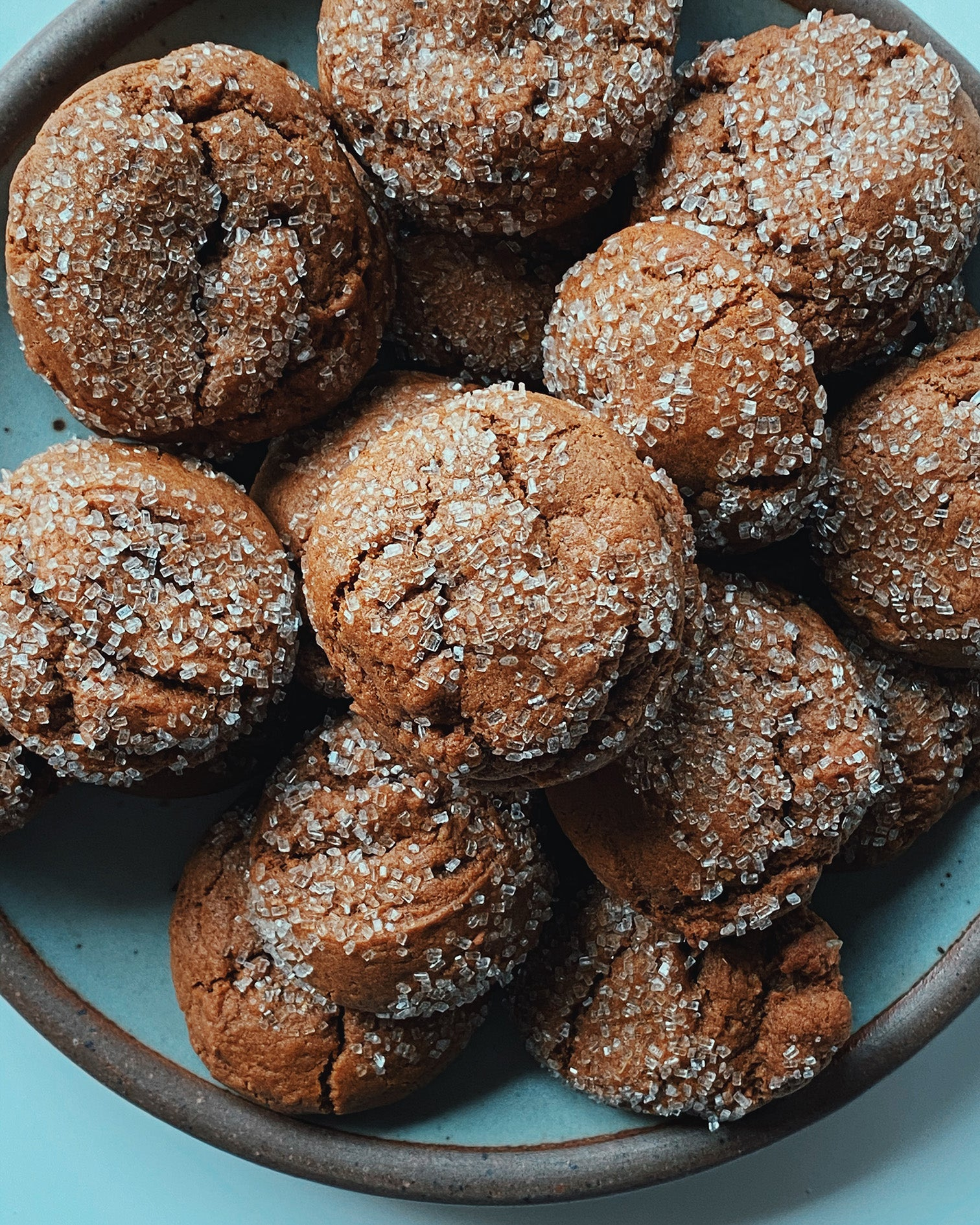 molasses masala snap cookies big pile of cookies with sugar twinkling in a blue bowl with brown edging