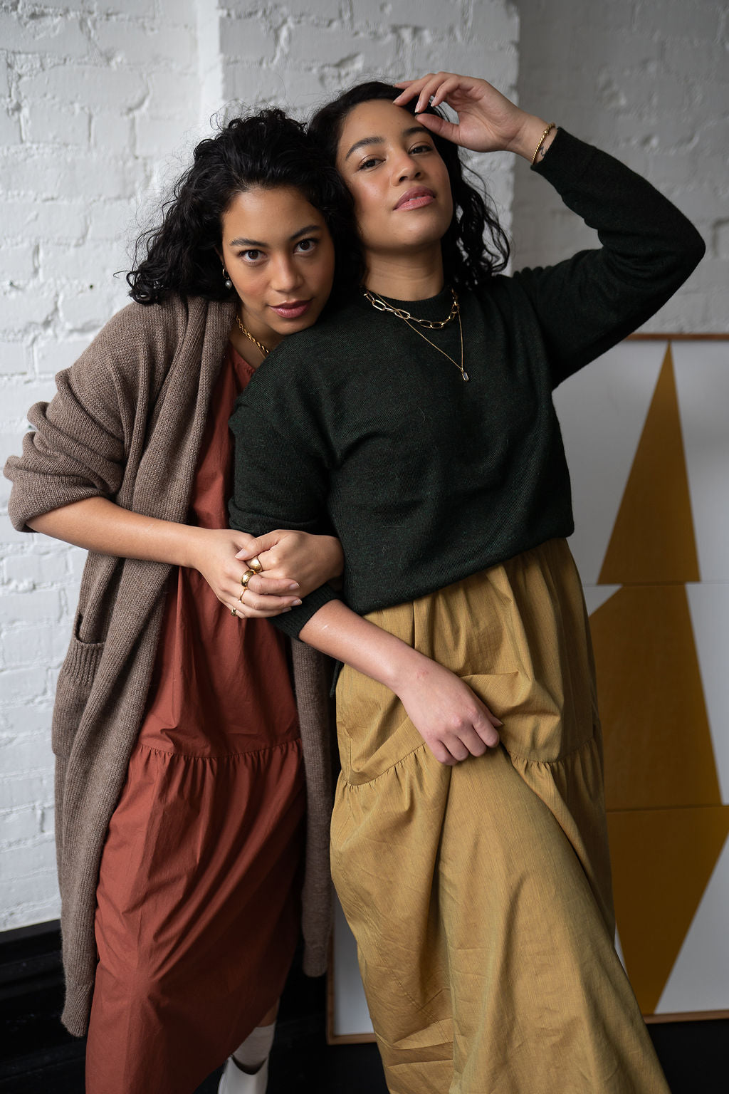 twin fashion bloggers embraced wearing tiered long cotton dresses in rust and yellow under oatmeal color cardigan and dark green pullover sweater white brick wall black floor art leaning against the wall gold jewelry