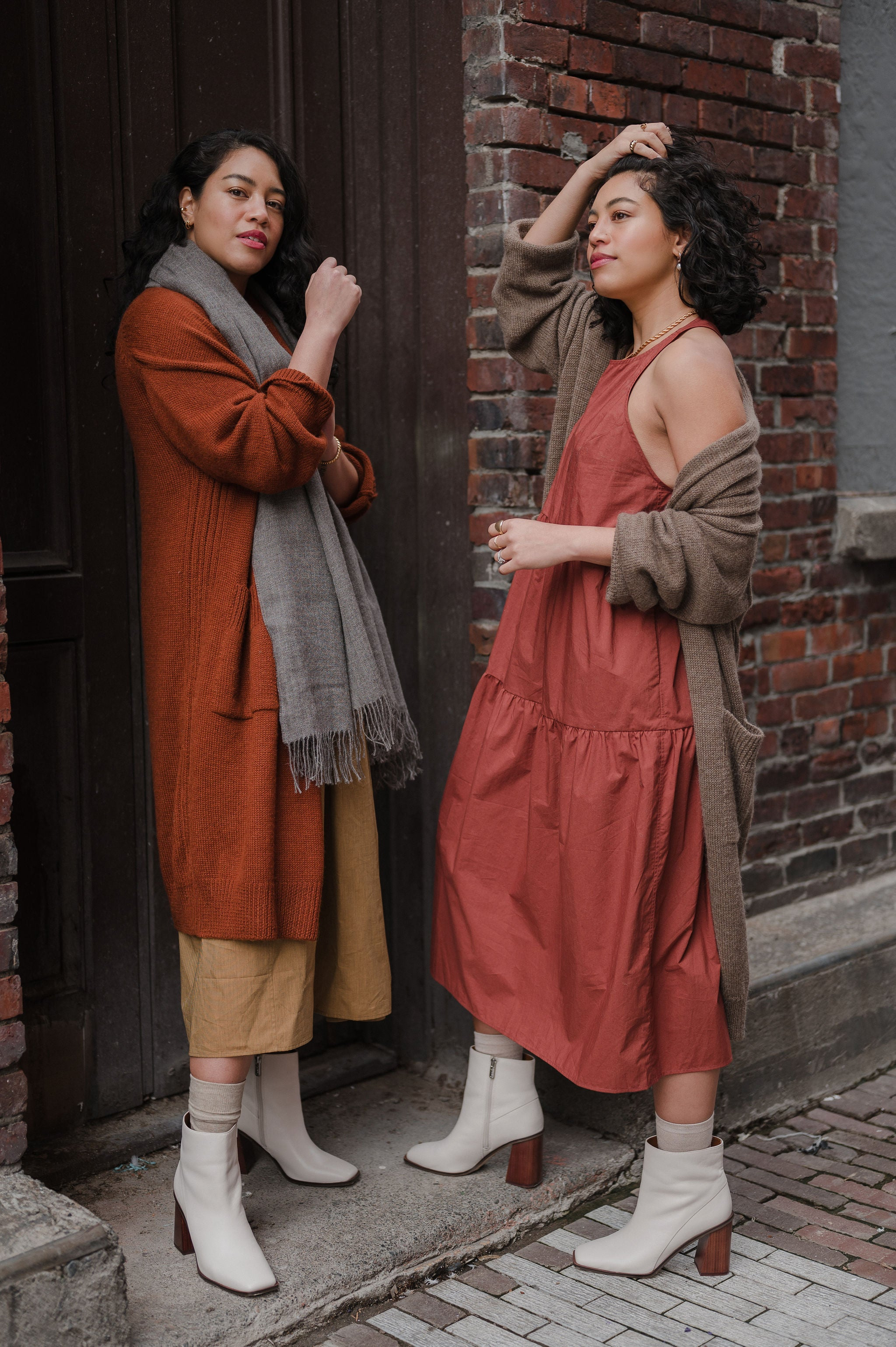 twin fashion women bloggers wearing long rust colored styles against a brick wall in alley. Long wheat colored cotton tiered dress under rust long baby alpaca cardigan with a grey scarf, both wearing white boots. The other twin wearing long rust cotton tiered dress with oatmeal colored cardigan and white boots pulling her hair off her face