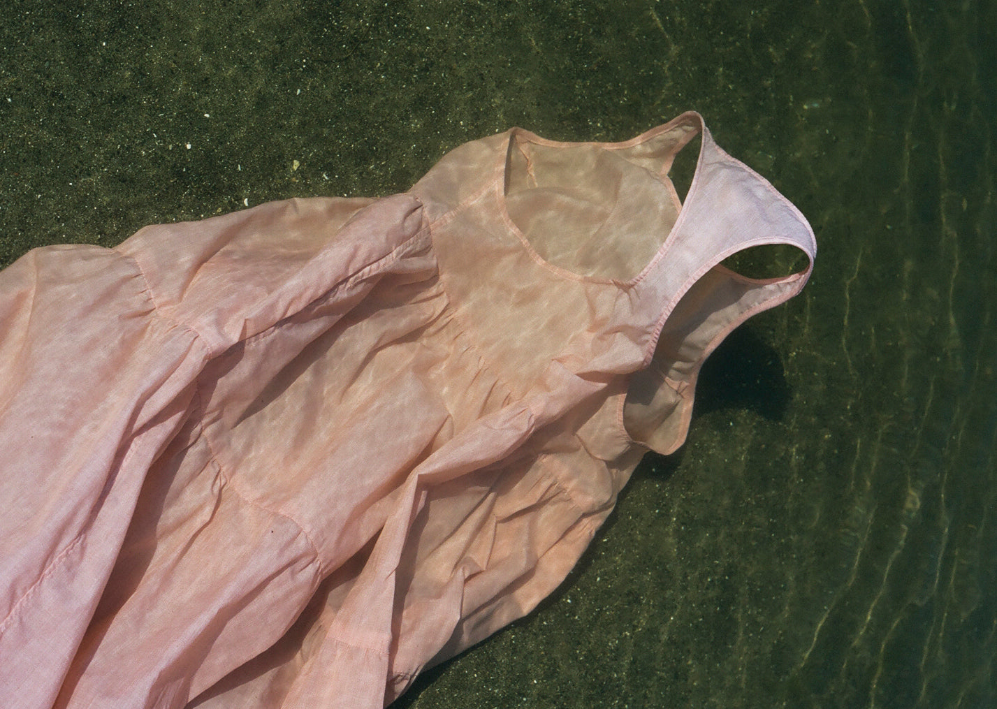Pale pink racerback ankle length tiered dress or nightdress floating underwater. The sand is green with flecks of metallic, you can see the waves and current in the sunlight. The dress is billowing in the movement of the waves.